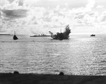 A destroyer escort dropping depth charges on a second Japanese Kaiten in the cruiser anchorage of Ulithi Lagoon on 20 Nov 1944 after the sinking of USS Mississinewa. Seen from USS Bunker Hill. Photo 3 of 3.