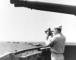US Navy Lt Robert S Selby shoots the sun with a sextant inside one of the 40mm gun tubs aboard seaplane tender USS Castle Rock, Tanapag Harbor, Saipan, Apr 1945. Note 40mm ammunition racks and PBM Mariners beyond.