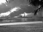 USS Nevada, down by the head, beached at Hospital Point in Pearl Harbor, Hawaii during the Japanese air attack on 7 Dec 1941. Note smoke from destroyer USS Shaw in the floating drydock just beyond Nevada.