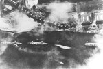 Japanese aerial photograph of the overturned USS Utah, sunk by torpedoes in the Japanese air attack on Pearl Harbor, Hawaii, 7 Dec 1941. Cruisers Detroit and Raleigh can be seen at left and USS Tangier at right.
