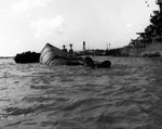 The overturned battleship USS Oklahoma, sunk by torpedoes in the Japanese air attack on Pearl Harbor, Hawaii, 7 Dec 1941. Maryland is at right and California's masts and Ford Island water tower are in the distance.