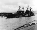 Battleships USS Tennessee (left, floating) and USS West Virginia (right, sunk) at Pearl Harbor's Battleship Row, 10 Dec 1941. The masts of the sunken USS Arizona can be seen behind the West Virginia.