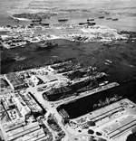 Aerial view of shipping in the Pearl Harbor Navy Yard repair basin with Ford Island beyond, 12 Dec 1943. Note the camouflage patterns painted on the roofs of the buildings.