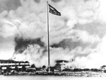 The American flag, battered and torn, flying at the Hickam Field barracks during the Pearl Harbor attack, Hawaii, 7 Dec 1941. This was one of the most published wartime flag photos until Joe Rosenthal's Iwo Jima photo.