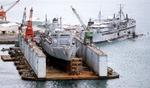 USNS Spica in drydock, Ship Repair Facility Subic Bay, Philippines, 1 Jan 1987; note USS Proteus tending two submarines