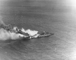 Aerial view of the USS Santa Fe close aboard the badly burning USS Franklin, 19 Mar 1945, southeast of Japan. Note Franklin's buckled forward elevator and the water streams from Santa Fe's stern onto the Franklin.