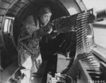 Staff Sergeant Maynard Smith at a machine gun in a B-17 bomber, mid-1943