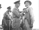 Lieutenant General Delos Emmons decorating an enlisted man for actions performed during the Japanese attack on Pearl Harbor. Hickam Field, 23 Dec 1941. Major General Clarence Tinker looking on.