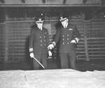 United States Coast Guard Captains Edward Fritzche (left) and Miles Imlay (right) examining a relief map of Omaha Beach laid out in the hold of the Attack Transport USS Samuel Chase, Jun 1944.