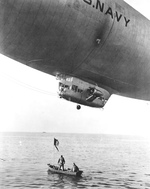 United States Navy K-class airship, probably based at Lakehurst, New Jersey, United States, engaged in a drill to lower supplies to survivors in a small boat, Jan 1943.