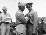 Captain Arleigh Burke receiving the Navy Cross from Rear Admiral Arthur Merrill aboard the destroyer Charles Ausburne in Purvis Bay, Florida Island, Solomons, 30 Jan 1944.