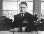 Portrait of Commodore Leslie Gehres sitting at his desk as commander of Fleet Air Wing Four, Adak, Alaska, mid-1944.