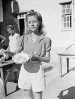 Wendy Pamela Rossini, recently freed Australian internee of Stanley Internment Camp, displaying the typical daily rice ration for her family of 5 during Japanese occupation, Hong Kong, Aug-Sep 1945