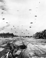 United States Army paratroopers landing on the Kamiri airstrip on Noemfoor Island off New Guinea, 3 Jul 1944. Note B-17 fortress patrolling high overhead.