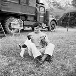 "General Bernard Montgomery relaxing with his traveling companions, a fox terrier puppy named ""Hitler"" and a spaniel puppy named ""Rommel,"" at his headquarters at Blay, Normandy, France, 6 Jul 1944."