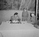 British Field Marshal Bernard Montgomery is the last to sign the documents of surrender as German General Eberhard Kinzel looks on at Montgomery's headquarters at Lüneburg Heath, Germany, 4 May 1945.