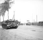 A Comet tank of British 11th Armored Division outside the gate of the Bergen-Belsen Concentration Camp as British troops were first arriving at the camp, 15 Apr 1945.