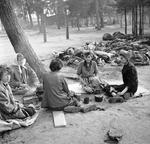 Women prisoners at the Bergen-Belsen Concentration Camp preparing food in the open air with scores of rotting corpses all around them, 17 Apr 1945 (food provided by the British). Photo 1 of 3.