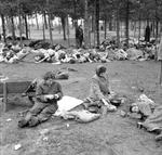 Women prisoners at the Bergen-Belsen Concentration Camp preparing food in the open air with scores of rotting corpses all around them, 17 Apr 1945 (food provided by the British). Photo 3 of 3.