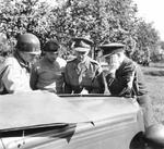 Generals Omar Bradley, Bernard Montgomery, and Miles Dempsey with Air-Marshal Trafford Leigh-Mallory in conference on the hood (bonnet) of Montgomery's Humber Super Snipe staff car, near St. Lô, Normandy, France, 5 Aug 1944.