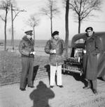 Field Marshal Bernard Montgomery and members of his staff stop on a Belgian road for a break, 27 Dec 1944. Note picnic set in trunk (boot) and the shadow of photographer Sgt John Morris.