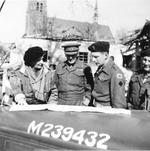 Field Marshal Bernard Montgomery, Major General Brian Horrocks, and Major R.P.P. Smyly examining a map on the hood (bonnet) of a staff car in the village of Marienbaum, Germany, 25 Mar 1945.