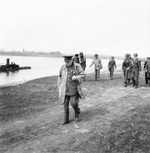After crossing the Rhine, British Prime Minister Winston Churchill walking along the river's eastern bank, 25 Mar 1945. Field Marshal Bernard Montgomery and some American generals can be seen in the background.