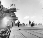 Smoke pouring out of the uptakes of the carrier USS Yorktown after being struck by Japanese bombs during the Battle of Midway, 4 Jun 1942.