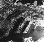Aerial view of Gotenhafen (Gdynia), occupied Poland, Jun 1942, photo 1 of 2; photo taken by a British RAF aircraft; note battlecruiser Gneisenau (white arrow) and carrier Graf Zeppelin (bottom)