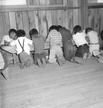Third grade arithmetic class with no desks or other school facilities at the Manzanar Relocation Center for deported Japanese-Americans, Inyo County, California, United States, 1 Jul 1942