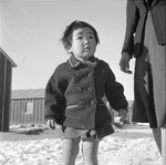 Young Japanese-American Sachi Ohira of El Monte, California walking with her mother at the Heart Mountain Relocation Camp in Wyoming, United States, 5 Apr 1943.