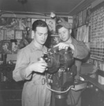 "Two bombsight technicians working on a Lucas Harold built Norden bombsight on a calibration stand, presumably in the Burma Theater circa 1944. Note the ""training material"" on the wall behind the technicians."