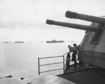 As seen from the flight deck of the USS Hancock near the No. 1 5-inch mount, sailors look at the nearby carriers Intrepid, Cabot, and Belleau Wood while anchored at Ulithi, Caroline Islands, 9 Nov 1944.