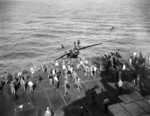 "F6F-5 Hellcat BuNo 71632 being ""surveyed"" over the side of USS Hancock after flipping onto its back from a barrier crash on landing following a strike against Iwo Jima, 21 Feb 1945. The pilot was not hurt."