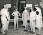 First lady Eleanor Roosevelt, center, upon arrival at Espiritu Santo, New Hebrides during her tour of the South Pacific on behalf of the Red Cross, 14 Sep 1943. Vice-Admiral Aubrey Fitch is to her left.