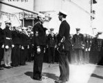 Ernest King, Captain of the USS Lexington (Lexington-class), making a presentation of cigarette cases to members of a Navy racing boat crew, 5 Sep 1931, probably at San Pedro, California.