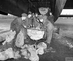 Groundcrew of No. 514 Squadron of Lancaster bombers at Waterbeach, Cambridgeshire, England loading food parcels into an airplane's bomb bay for dropping on the Netherlands during Operation Manna, May 1945.
