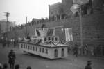 Lunar New Year parade, Chongqing, China, 15 Feb 1942; note Chinese and American national flags on float, Nationalist Party flag behind utility pole, Nationalist Party flags behind float