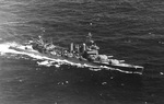 Aerial view of USS New Orleans during exercises in Hawaiian waters, 8 Jul 1942. Note all main guns trained to port.