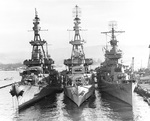 Cruisers USS Salt Lake City, Pensacola, and New Orleans nested together at Pearl Harbor in Berth B-3, 30 Oct 1943. Note the radar antennae, gun directors and eight-inch guns on these three heavy cruisers.