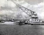 USS Current alongside Pearl Harbor Salvage Dock as Floating Crane YD-121 lifts a Japanese Type A Kō-hyōteki-class midget submarine used in the Pearl Harbor Attack salvaged from Oahu's Keehi Lagoon, 14 Jul 1960.