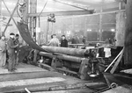 Shipfitters in one of the shops at the Puget Sound Naval Shipyard, Bremerton, Washington, United States rolling steel plate with assistance from the overhead jib crane, 1918.