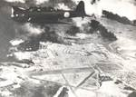 B5N2 torpedo bomber flying above Pearl Harbor, 7 Dec 1941 at 0920; Hickam Field in foreground below and burning American ships in background
