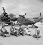British pilots resting at Luqa airfield, Malta,  Jan 1943; note Beaufighter and Spitfire Mk VC aircraft in background