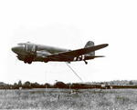 C-47 Skytrain aircraft recovering a CG-4A glider, Normandy, France, 23 Jun 1944; note hooked tow line from C-47 getting ready to hook onto a net connected to glider