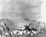 Crew of USS Oriskany fighting a fire caused by a F4U-4 Corsair fighter landing accident, off Korea, 6 Mar 1953