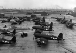 F4U-1 Corsair, FM-2 Wildcat, SNC-1 Falcon, and Culver TD2C aircraft at Naval Air Station Long Beach, California, United States, 10 Aug 1944; note SB2C Helldiver aircraft in background behind pile