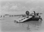 US Marines wading past wreckage of a D3A dive bomber, Agat beachhead, Guam, Mariana Islands, Jul 1944