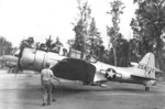 RA-24B-15-DT Banshee aircraft (serial number 42-54736) preparing for take off on Morotai in the Moluccas, 1 Jan 1945; note C-47 Skytrain and hulk of C-45 Expeditor fuselage