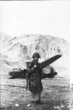 German glider trooper posing with a FG 42 rifle before a DFS 230 C-1 glider, Gran Sasso, Italy, 12 Sep 1943